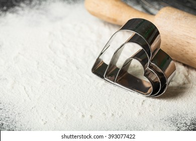 Metal forms for Christmas cookies: heart on wooden table with flour with rolling pin on table.