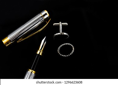 Metal fountain pen with men's luxury cufflinks on a black isolated background. Conceptual male dilovy style, business project
