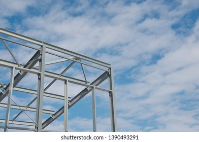 Metal frame of the new building against the blue sky with clouds