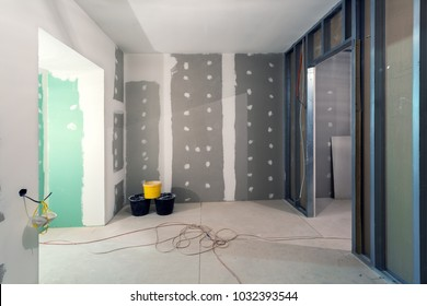 Metal frames and plasterboard (drywall) for gypsum walls, three buckets and electric wires  in apartment is under construction, remodeling, renovation, extension, restoration and reconstruction