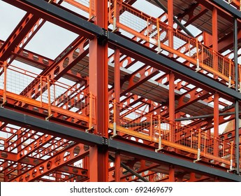 metal framework of new building development with a network of orange steel girders  and safety fencing