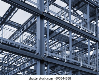 metal framework of new building development with a network of blue steel girders  and safety fencing.