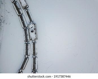 Metal gangways in a frozen industrial port. Aerial drone view. Winter snowy day.