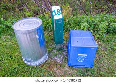 A metal garbage can and blue recycle bin sit upside down by a campsite post in a Provincial Park in Newfoundland, Canada where they offer garbage and recycle pickup services right at each campsite.