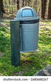 A metal garbage can with a plastic bag inside and a dome enclosure attached to a cement post outdoors in a wooded park on a sunny day in springtime