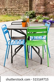 Metal garden furniture of table and chairs on a patio or street restaurant.