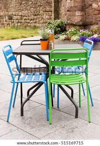 metal garden furniture of table and chairs on a patio or street restaurant - Garden Table A Chairs