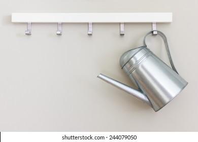metal garden watering pot hanging on the wall