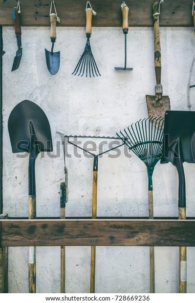 Metallgärtnerwerkzeuge, die auf einen Steckplatz aus Holz gestellt werden, und aufhängen an Nägeln. Beispiele für Werkzeuge sind Schaufel, Spaten, Harrow, Rake und Schaufelgabeln. Filtereffekt von Vintage-Filmen. Geschichten über landwirtschaftliche Geräte