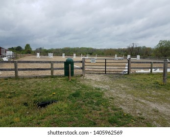 metal gate and garbage can at equestrian arena