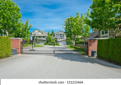 Metal gates with some residential houses behind in a nice and quiet neighborhood in the suburbs of Vancouver, Canada.
