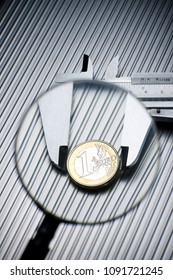 metal gauge measuring a one euro coin on a metal surface.