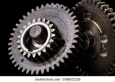 Metal gears from an internal combustion engine. Torque transmitting components. Dark background.