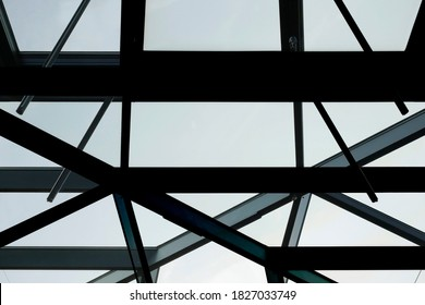 Metal girders as load-bearing structures of transparent wall or ceiling. Close-up of glass office building framework fragment. Abstract modern architecture background in hi-tech style.