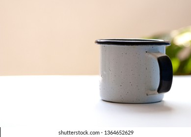 Metal glass or cup of cold water with ice on stainless steel table background.  Vintage cup of enamel stands on wooden desk during work . Pewter cup