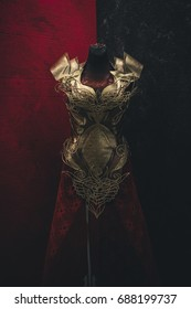 Metal Golden armor for women. Carries pieces of gold and fabrics and feathers in red color