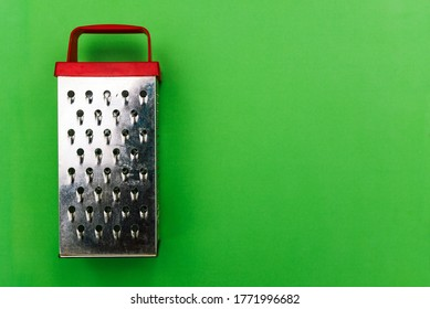 Metal grater with a red handle on a green background. Grater for vegetables and products. Kitchen grater close-up with a copy of the space. A top view of a flat layout. Cooking.