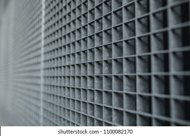 Metal gray lattice with small square cells grid stock background with selective focus