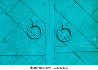 Metal green aged textured door with rings door handles and metal details. Metal architecture background.Old green door with rivets and aged metal door handle in the form of ring
