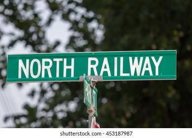 Metal Green North Railway Street Sign against dark background