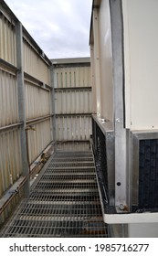 Metal grid access walkway around a cooling tower enclosed on a rooftop with water leak at intake louvres