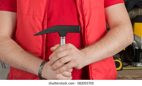 metal hammer in the hands of the worker on the background of the workplace