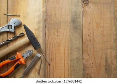 Metal hammer, pliers, screwdriver on an old workbench, place for inscription