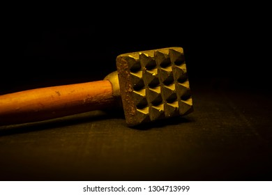 A metal hammer with a wooden handle for meat.