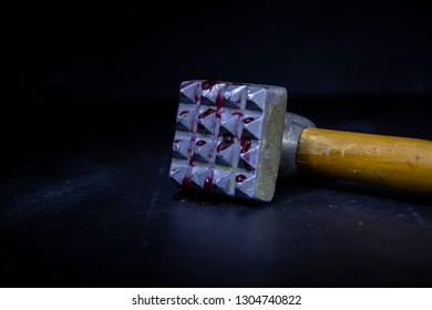 A metal hammer with a wooden handle for meat. Blood,