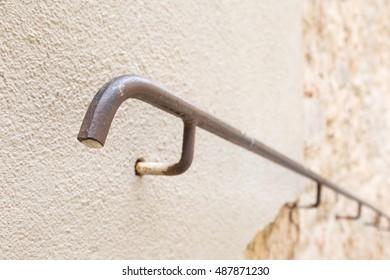 Metal handrail on a broken wall leading downwards