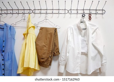 Metal hanger on a white wall. On a hanger are four trempels with clothes: a blue sundress, brown trousers, a white shirt, a yellow dress.  Multi-colored women's clothing, summer wardrobe