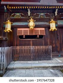 The metal tsuri–doro hanging lanterns hang from the eaves of a roof of the Shaden Sanctuary of Kitano Tenmangu shrine. Kyoto. Japan