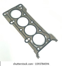 Metal head gasket for four cylinder engine on white background