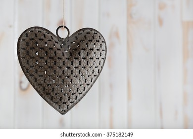 A metal heart hanging on a piece of string against a white wooden background