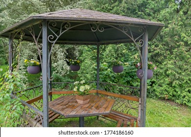 Metal hexagonal gazebo with ornate elements, with wooden benches around perimeter, wooden table in middle, with vase of white flowers on it and gray wicker baskets with flowers around, among trees