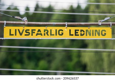 Metal high voltage danger sign and railway electric overhead contact wire all over. In swedish