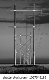 Metal  and high voltage electrical power transmission pole structures  running through farmer's fields carrying electricity and electrical energy to supply Saskatchewan users and industries.