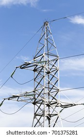 Metal high-voltage pole of an open switchgear with a glass linear insulator photographed against a blue sky close-up.