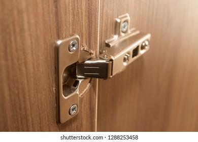 Metal hinge on a wooden wardrobe.