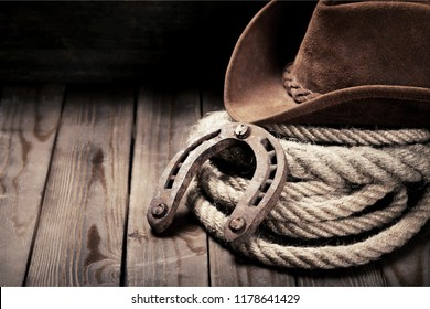 Metal horseshoe and cowboy hat on wooden