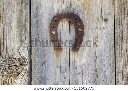 Metal Horseshoe Hanging On Wooden Door