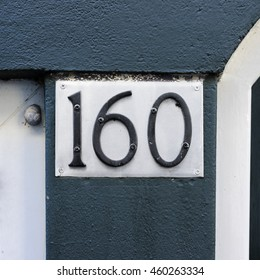 metal house number one hundred and sixty attached to a metal plate with rivets