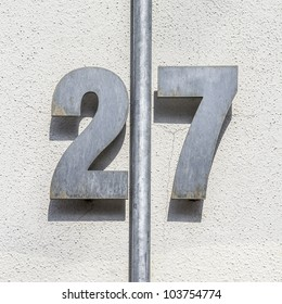 metal house number twenty-seven, divided by a vertical pipe.