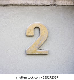 metal house number two on a white stucco wall