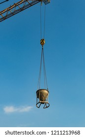 Metal industrial bowl with a load of concrete or mortar hangs in the sky on chains and ropes of a tower crane. Part of the crane beam is visible. Small white cloud left of the bowl. Vertical image