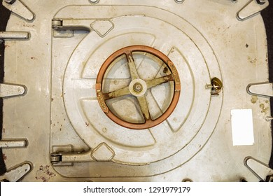 Metal industrial submarine door hatch painted white with worn red handle.