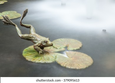 A metal jumping frog sculpture. Long exposure.