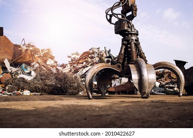 Metal junk yard with hydraulic lifting machine with claw attachment for scrap metal lifting.