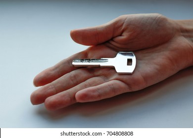 The metal key from the apartment in a female hand. Closeup