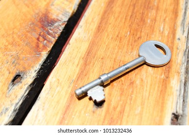 Metal Key Glinting in the Sun on a Wooden Table